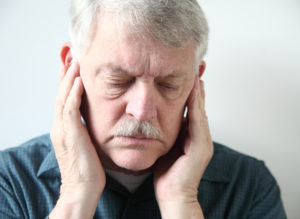 older man holding painful jaw